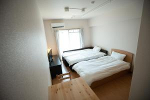A bed or beds in a room at HOTEL REJOICE STAY Kyoto Karasuma Oike