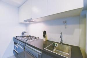 A kitchen or kitchenette at HFN Southern Cross Apartment
