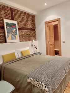 Un pat sau paturi într-o cameră la Aspasios San Mateo Boutique Apartments