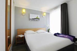 Un ou plusieurs lits dans un hébergement de l'établissement Aparthotel Adagio Access Marseille Prado Périer