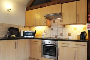 A kitchen or kitchenette at New Inn Lane Holiday Cottages