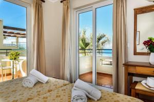 A bed or beds in a room at Panos Beach Hotel