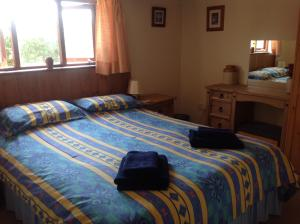 A bed or beds in a room at New Stable Cottage