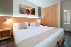 A bed or beds in a room at Hotel Club Siroco - Adults Only