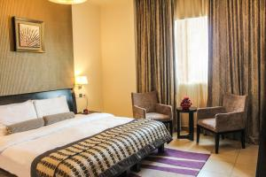 A bed or beds in a room at Dunes Hotel Apartment Oud Metha