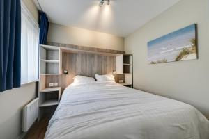 A bed or beds in a room at Holiday Suites De Haan