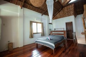 A bed or beds in a room at Surfing Carabao Beach Houses