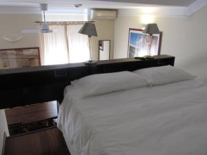 A bed or beds in a room at Rex Hotel Residence