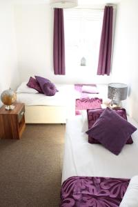 A bed or beds in a room at Empire Serviced Apartments