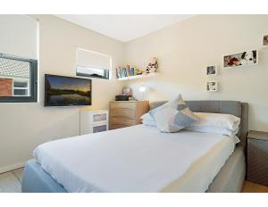 A bed or beds in a room at Quiet, sunny apartment close to beach and bush