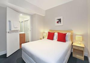A bed or beds in a room at AeA Sydney Airport Serviced Apartments