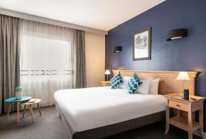 A bed or beds in a room at Aparthotel Adagio La Défense Esplanade