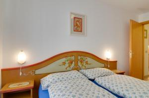 A bed or beds in a room at Appartamenti Cesa Maria Mountain Hospitality