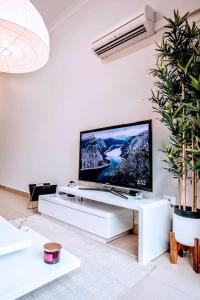 A television and/or entertainment center at BRAND MODERN STUDIO W/BALCONY BBQ in Best Spot - BONDI BEACH