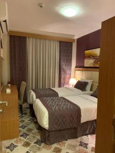 A bed or beds in a room at Altelal Apartment