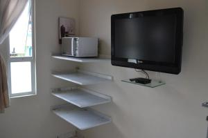 Uma TV ou centro de entretenimento em Casa Condominio 250M Praia Maranduba Wifi Churrasqueira