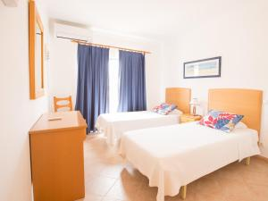 A bed or beds in a room at Apartamentos Quinta da Praia