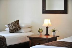 A bed or beds in a room at Verandahs Boutique Apartments