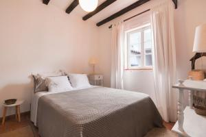 A bed or beds in a room at Casa Lamelas - Porto Covo