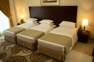 A bed or beds in a room at Rose Garden Hotel Apartments - Barsha