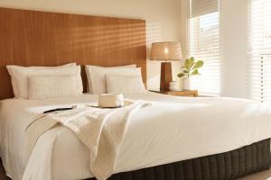 A bed or beds in a room at Sea Change Beachfront Apartments