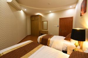 سرير أو أسرّة في غرفة في كليمانس للأجنحة الفندقية