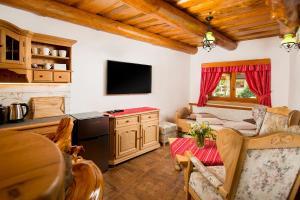 Televízia a/alebo spoločenská miestnosť v ubytovaní Apartmány Kubínska hoľa - ZRUB