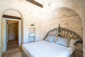 A bed or beds in a room at Trulli Ad Maiora