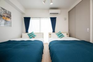 A bed or beds in a room at Riverside Inn Hakata