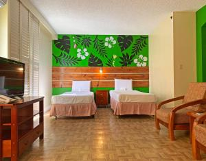 A bed or beds in a room at Garden Villa Hotel