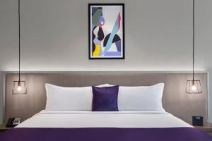 A bed or beds in a room at Leva Hotel and Suites, Mazaya Centre