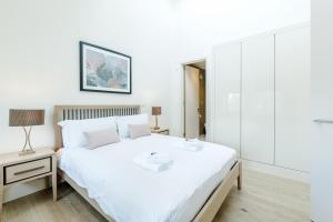 A bed or beds in a room at LCS Shoreditch Apartments