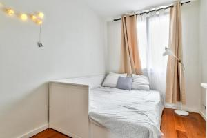 A bed or beds in a room at Cozy apartment for 4 people near Buttes Chaumont
