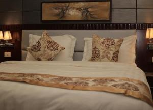 A bed or beds in a room at The 40th Pearl Hotel Suites