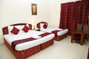 A bed or beds in a room at Sahara Hotel Apartments