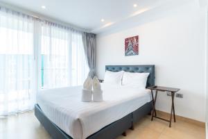 Кровать или кровати в номере Central Avenue Residences by Pattaya Holiday