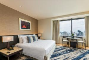A bed or beds in a room at Emporium Suites by Chatrium