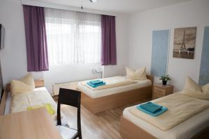 A bed or beds in a room at Pension Nuernberg-Fuerth