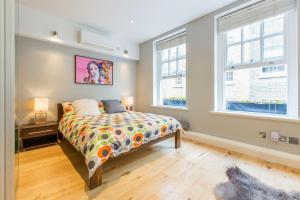 A bed or beds in a room at London Holiday Apartments