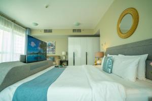 A bed or beds in a room at A C Pearl Holiday - Stunning Marina and Sea Views Apartment