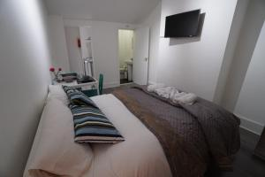 A bed or beds in a room at London Queen's Park Apartment