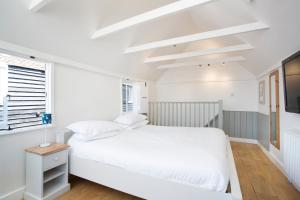 A bed or beds in a room at Whitstable Fisherman's Huts and Warehouse Cottages