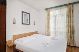 A bed or beds in a room at Apartments Astra Plava Laguna