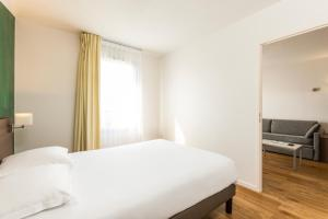 A bed or beds in a room at Aparthotel Adagio Access Carrières Sous Poissy