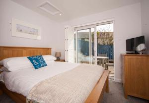 A bed or beds in a room at Mawgan Porth Apartments