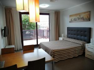 A bed or beds in a room at Aparthotel El Faro