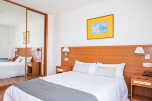 A bed or beds in a room at Aparthotel Playas de Liencres