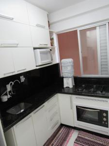 A kitchen or kitchenette at Apartamento Coral - 1 quadra do Mar