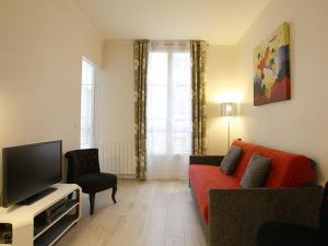 Uma TV ou centro de entretenimento em Apartments Paris Centre - At Home Hotel