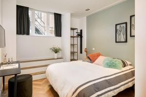 A bed or beds in a room at Damrak Short Stay Amsterdam